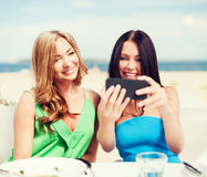 Girls taking photo in cafe on the beach Stock Image