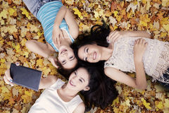 Girls taking photos on autumn leaves. Unique perspective of three teenage girls taking picture with smartphone while lying down on autumn leaves Royalty Free Stock Photography