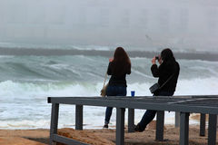 Girls taking photos of a sea storm.  Stock Photos