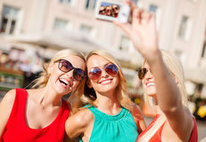 Girls taking picture with camera in the city Stock Photography