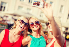 Girls taking picture with camera in the city Royalty Free Stock Images