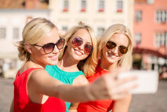 Girls taking picture with smartphone camera Stock Images