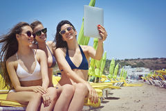 Girls taking pictures at the beach Royalty Free Stock Photos