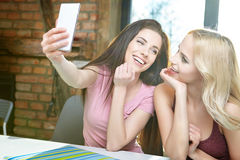 Girls taking pictures on the phone at home Royalty Free Stock Images