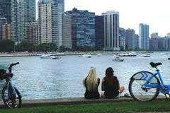 Girls Taking A Rest In Downtown Chicago. Girls taking a rest from riding their bikes along the Lake Michigan to look at the Chicago city skyline Stock Images