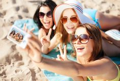 Girls taking self photo on the beach Stock Photography