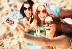 Girls taking self photo on the beach Royalty Free Stock Photos