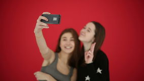 Girls taking self portrait with smart phone watch photos smile and laugh. Red studio background stock video
