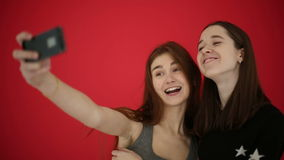Girls taking self portrait with smart phone watch photos smile and laugh. Red studio background stock footage