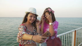 Girls taking selfie on the pontoon with the sea as a background. Girls taking selfie on a pontoon with the sea as a background stock video footage
