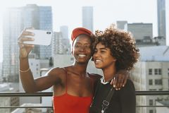 Girls taking a selfie at a rooftop stock images