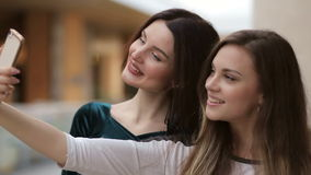 Girls taking selfie in shopping center, close-up. Two young attractive girls taking selfie in shopping center, close-up stock footage