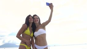 Girls taking selfie using phone on beach smiling. Hug each other stock video