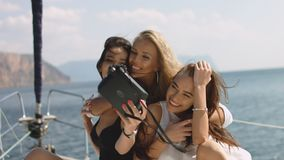 Girls taking selfies on yacht. Young models on vacation stock video