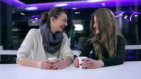 Girls talking in cafe. Two beautiful girls talking in cafe. Girlfriends drinking coffee and talking in cafe. Girls talking in cafe. Girlfriends gossiping in a stock footage