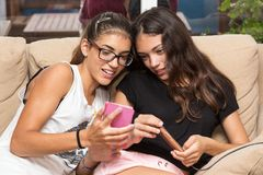 Girls talking about an image they see on the mobile. Two girls watching a picture on the phone, both smile and seem to converse Royalty Free Stock Image
