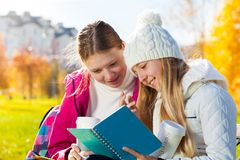 Girls talking looking to textbook. Close portrait of two happy 14 years old girls in the autumn park taking about homework holding textbook and coffee Stock Image