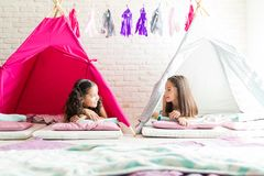 Girls Talking While Lying In Tipi Tents During Slumber Party. Preteen girls talking while lying in tipi tents during slumber party at home royalty free stock photography