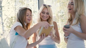 The girls are talking near the window. Two blondes are looking in the smartphone. The girl say words and three girls are laughing and start looking at the tablet stock footage