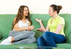 Girls talking on sofa Stock Image