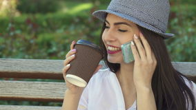 Girls talks on the phone on the bench stock footage