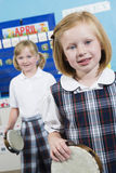 Girls With Tambourine In Music Class Royalty Free Stock Photos