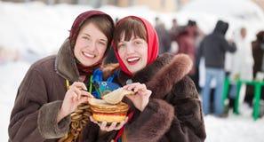 Girls  tasting pancake  during  Shrovetide Royalty Free Stock Photo