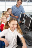 Girls and teacher in school class. Smiling to camera Royalty Free Stock Image