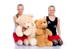 Girls with a teddy bear. Lovely little girls. Next to a large teddy bear on a white background in the studio. The concept of holidays, happy childhood. Isolated stock images
