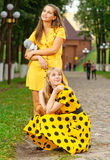 Girls with teddy bears. Two girl-friends in yellow dresses hold in hands of toy bears Royalty Free Stock Photo