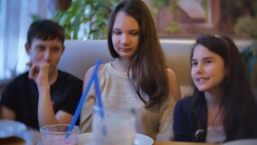 The girls teen communicate in a cafe are friends. children teens sitting in cafe fast food indoors slow motion video. The girls teen communicate in cafe are stock video