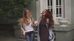 Girls teenagers carelessly dance on the street and listen to music on headphones. slow motion stock video footage