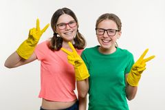 Girls teenagers wearing yellow protective gloves show victory. stock image