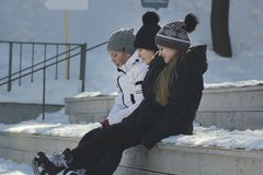 Girls Teens wearing skates sit on a bench near the rink and talking. Youth pastime and rest Stock Photography