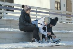 Girls Teens wearing skates sit on a bench near the rink and tightening the laces. Youth pastime and rest Stock Images