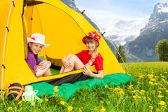 Girls in tent. Two happy laughing little girls sitting in camping tent in mountain yellow field Stock Photography