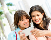 Girls texting from a phone Stock Photos