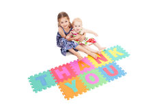 Girls with thank you sign. Two girls saying thankyou with letter tiles. Isolated on white royalty free stock image