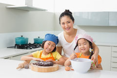 Girls with their mother preparing cookies in kitchen Stock Photography