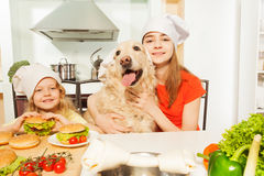 Girls with their pet in cook's hats preparing meal Stock Photos