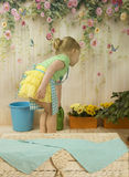 Girls  of three years care for flowers,. Two charming girls twins of three years play gardeners, water a yellow primrose in a pot, a beautiful, life-pleasing Stock Photography