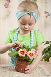 Girls  of three years care for flowers, Royalty Free Stock Photos