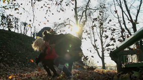 Girls throw leaevs into the air and jump from the bench at the same time. Two young women jump, throw, run and kick the autumn leaves high into the air stock video footage