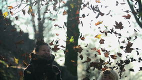 Girls throw leaves high into the air at the same time shot in slow motion. Two young women throw, run and kick the autumn leaves high into the air stock video
