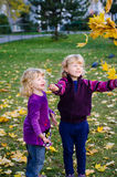 Girls throwing autumn leaves. Two blond girls throwing an autumn leaves Royalty Free Stock Photos