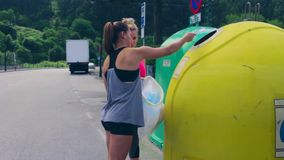 Girls throwing garbage to recycling dumpster stock footage