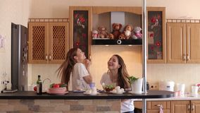 Girls throws food and trying to catch it in mouth. Two cheerful happy girls cook vegetable salad in the kitchen, they throw food and try to catch it with their stock video footage