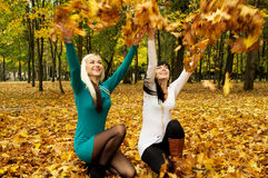 A girls throws leaves Royalty Free Stock Photo