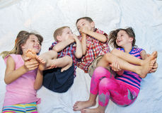 Girls tickling boys feet. Four children giggling playing Royalty Free Stock Photo
