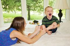 Girls tickling child's foot. Girl tickling boys foot while he laughs Stock Images